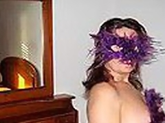 Chubby Spanish older woman in cute bra with multicolor heart shaped patterns blows strapon wearing a bizarre violet feather mask and listening to Santana's rendition of 'Black Magic Woman'.